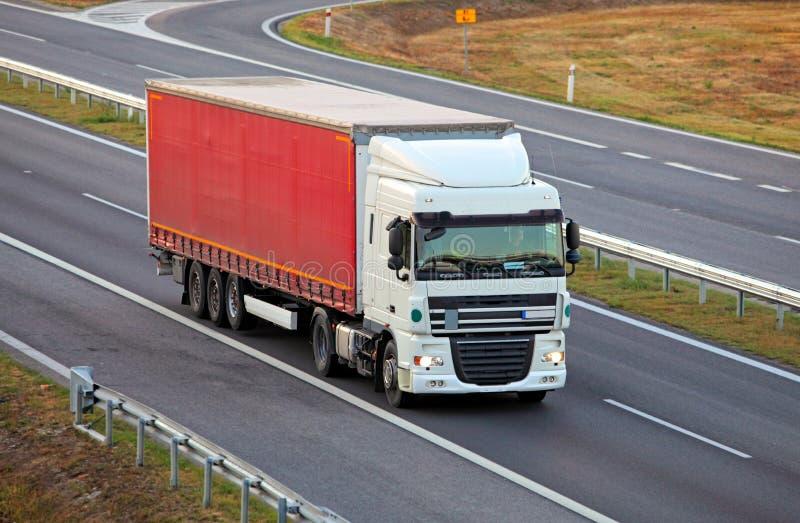 Ciężarówka na autostradzie, przewozi samochodem zdjęcie royalty free