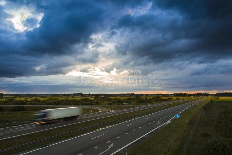 Ciężarówka w ruchu na autostradzie w mętny, barwny letni wieczór zdjęcia royalty free
