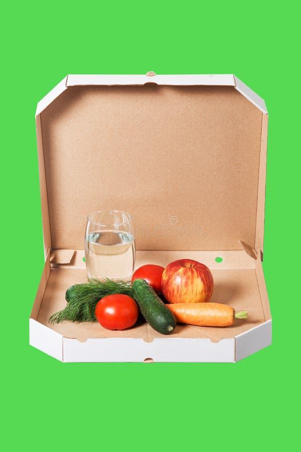 Ciężar strata i zdrowy pojęcie łasowania lub dieting Otwarty pizzy pudełko z surowymi warzywami i szkłem woda w nim obraz stock