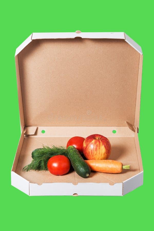 Ciężar strata i zdrowy pojęcie łasowania lub dieting Otwarty pizzy pudełko z surowymi warzywami w nim odizolowywał na zielonym tl obraz royalty free
