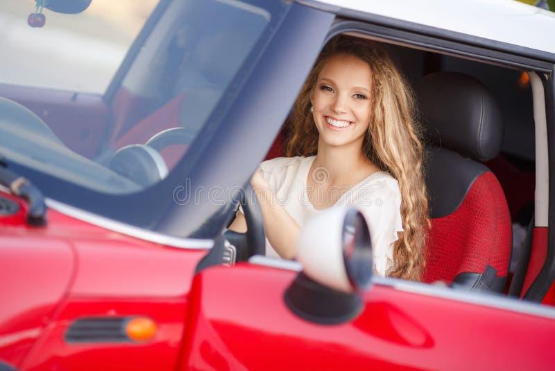 Ciężarna brunetki dziewczyna i jej czerwony samochód obrazy stock