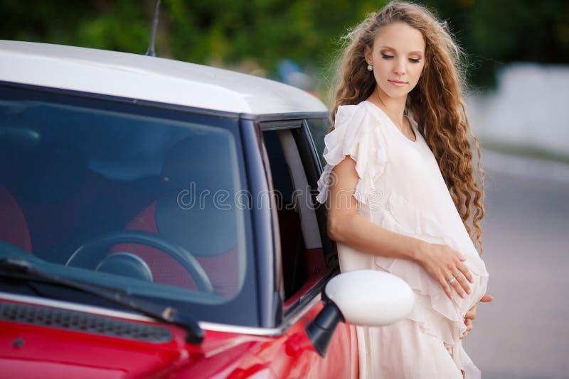 Ciężarna brunetki dziewczyna i jej czerwony samochód zdjęcia royalty free
