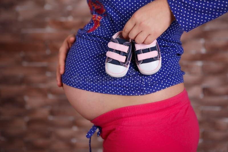 Ciężarna damy kobieta pozuje przód kamery ostrość z małymi dziecko butami w rękach jest ubranym sport domową colourful odzież i t zdjęcie royalty free