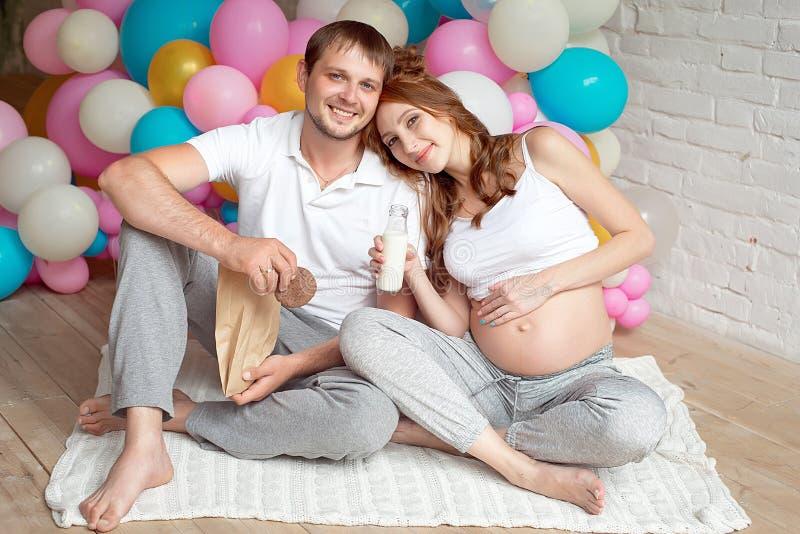 Ciężarna dziewczyna siedzi na podłoga z mężem zdjęcia stock
