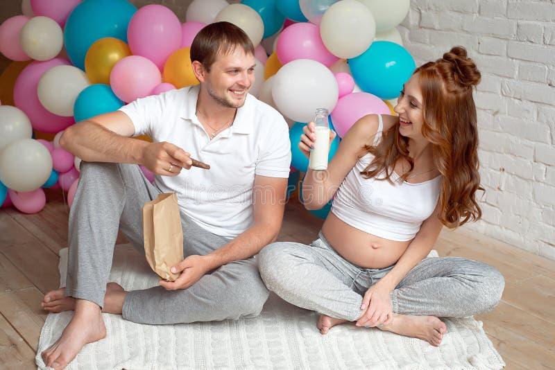 Ciężarna dziewczyna siedzi na podłoga z mężem fotografia stock