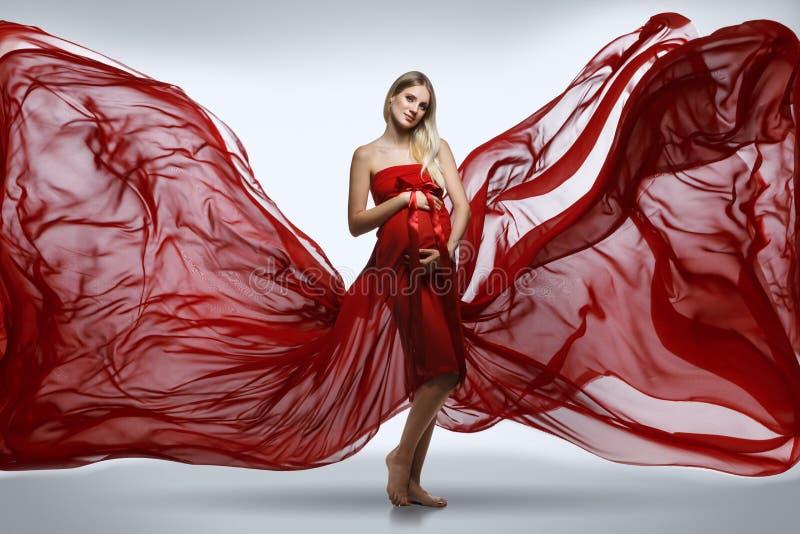Ciężarna dziewczyna w czerwieni sukni zdjęcie royalty free