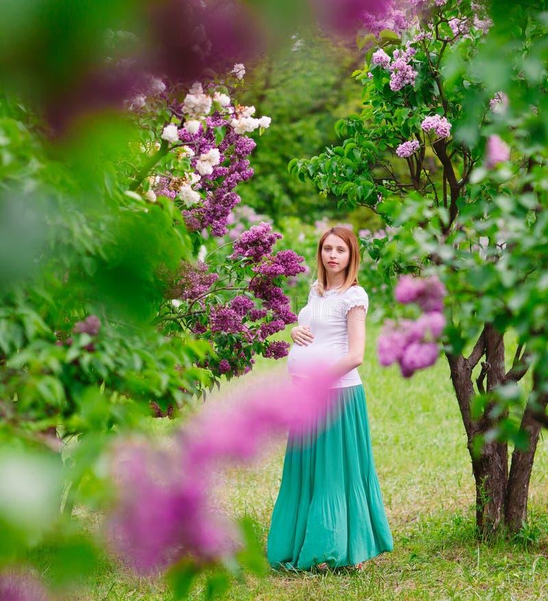 Ciężarna dziewczyna w lato parku outdoors obrazy stock