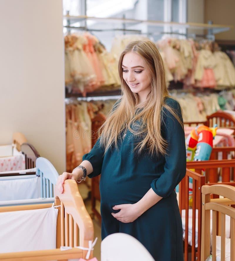 Ciężarna dziewczyna wybiera dziecka łóżko polowe w sklepie zdjęcie royalty free