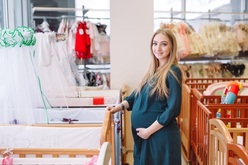 Ciężarna dziewczyna wybiera dziecka łóżko polowe w sklepie obrazy royalty free