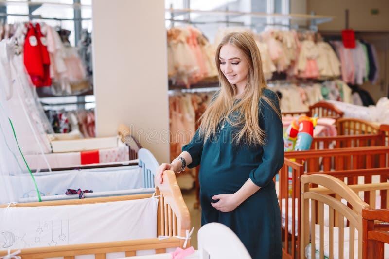 Ciężarna dziewczyna wybiera dziecka łóżko polowe w sklepie obrazy stock