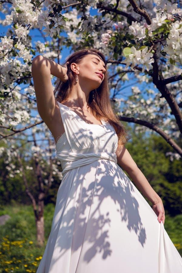 Ciężarna dziewczyna z długie włosy będący ubranym białą smokingową pozycję obrazy stock