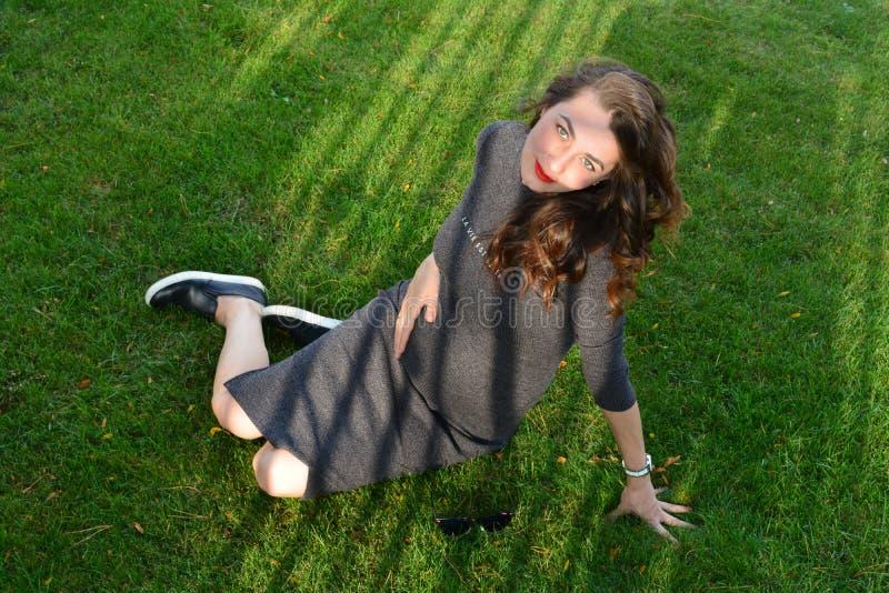 Ciężarna młoda kobieta siedzi na zielonej trawie w parku obrazy royalty free