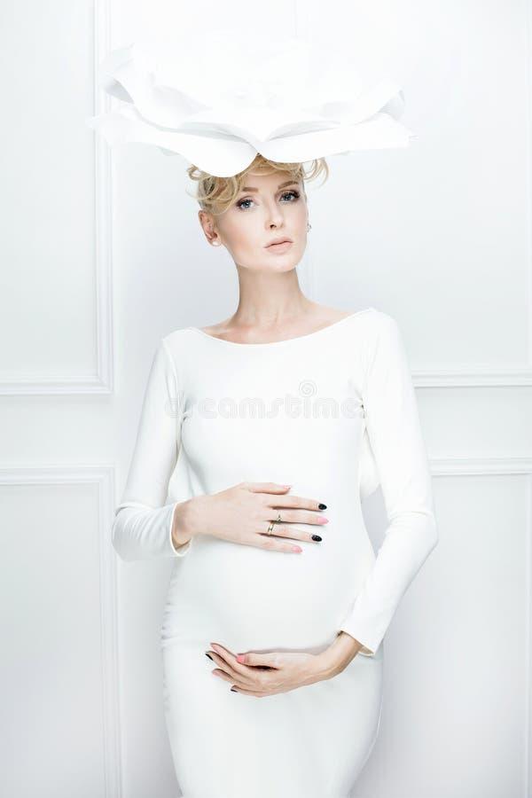 Ciężarna piękna kobieta pozuje w bielu zdjęcia stock