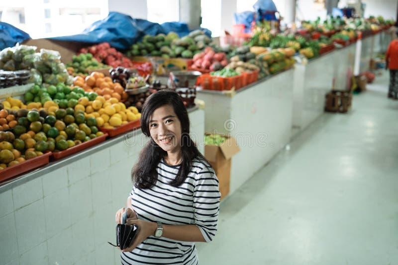 Ciężarni młodej kobiety przewożenia portfle płacić dla towarów fotografia stock