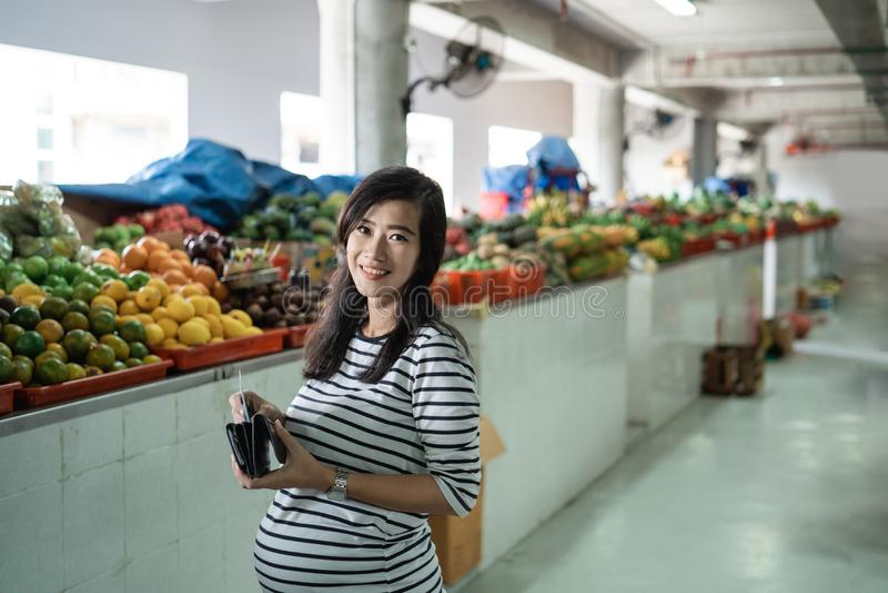 Ciężarny azjatykci kobieta wp8lywy pieniądze z jego portfla płacić dla towarów zdjęcia royalty free