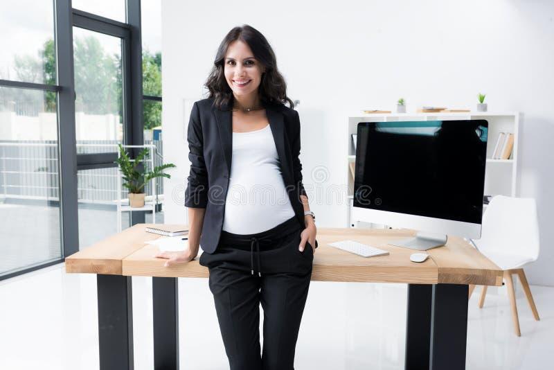 ciężarny bizneswoman oparty na worktable przy nowożytnym z powrotem zdjęcie stock
