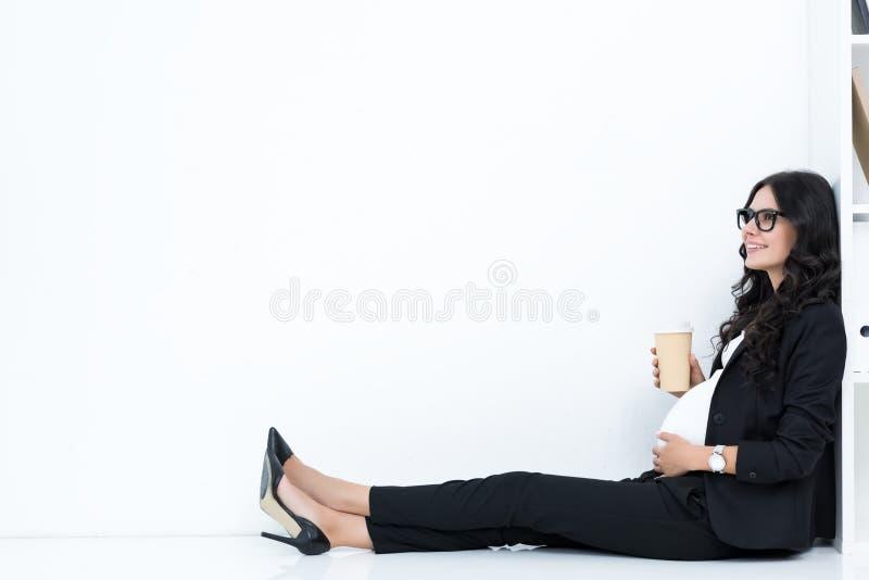 ciężarny bizneswoman pije kawę od papierowej filiżanki podczas gdy siedzący fotografia stock