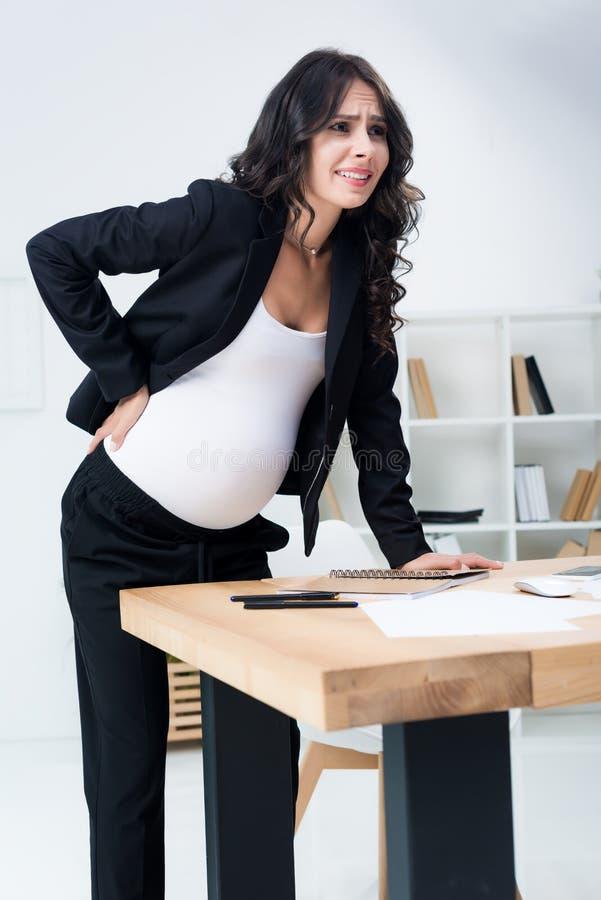 ciężarny bizneswoman z bólem pleców przy miejscem pracy w nowożytnym fotografia royalty free