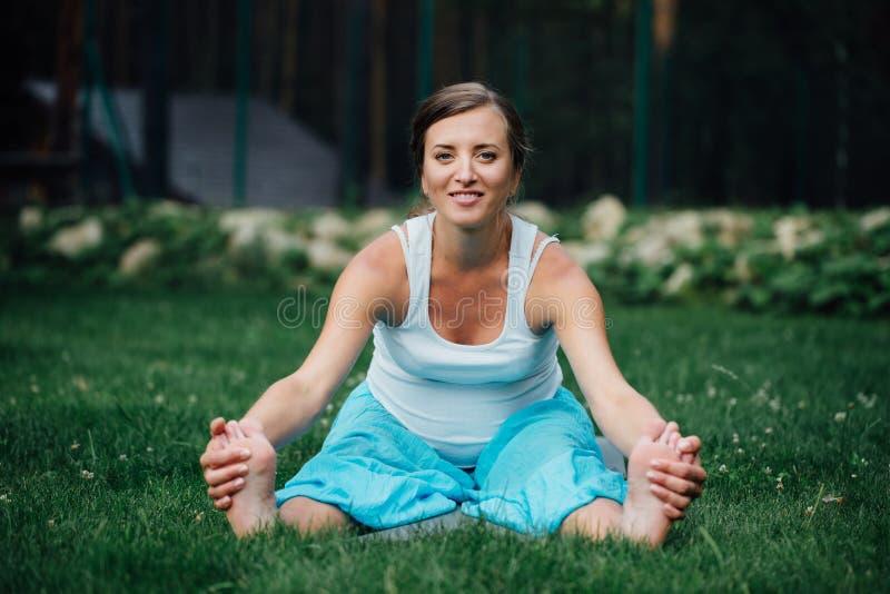 Ciężarny joga w lotosowej pozyci na lasowym tle w parku trawa, plenerowa, zdrowie kobieta zdjęcie stock