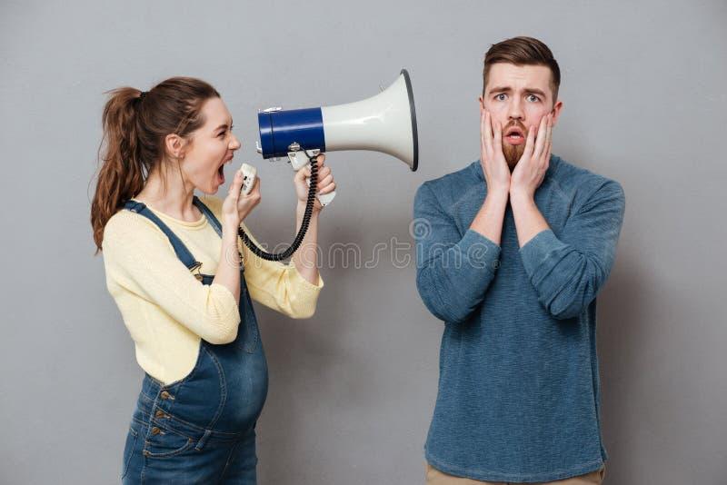 Ciężarny krzyczący kobiety mienia głośnik stoi blisko mężczyzna zdjęcia royalty free