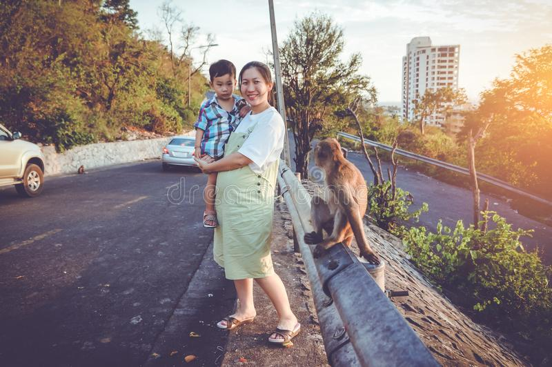 Ciężarny uśmiechać się jej syna blisko dżungli małpy i nieść Vintag fotografia royalty free