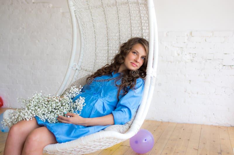 Ciężarny uśmiechnięty kobiety obsiadanie w krześle fotografia royalty free