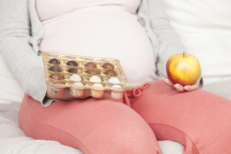 Ciężarny z cukierkiem i jabłkiem zdjęcia royalty free