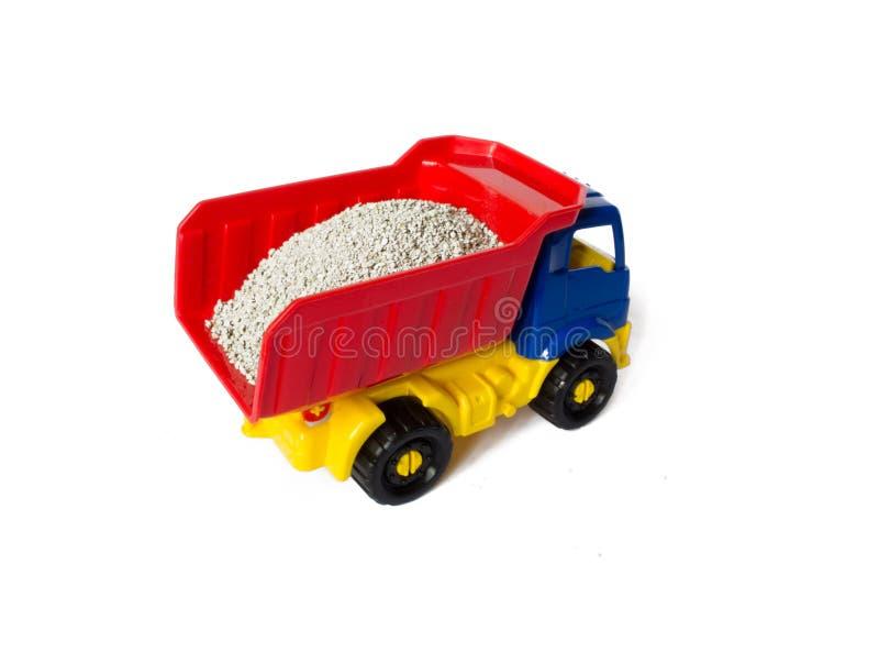 Ciężarowy zabawkarski samochód dla dzieci na białym odosobnionym tle samochód niesie ładunek zdjęcie stock