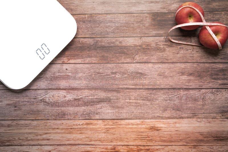 Ciężaru szalkowy biały cyfrowy z diety czerwoną jabłczaną zmorą z pomiarową taśmą na drewnianym tło sprawności fizycznej i zdrowi obraz stock