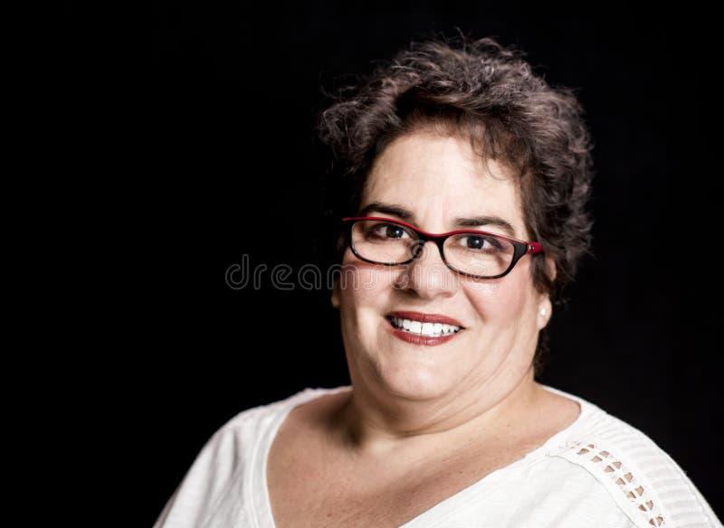 Ciężka Ustalona w średnim wieku kobieta jest ubranym szkła w studiu fotografia stock