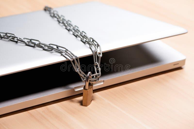 Ciężki łańcuch z kłódką wokoło laptopu na stole obraz stock