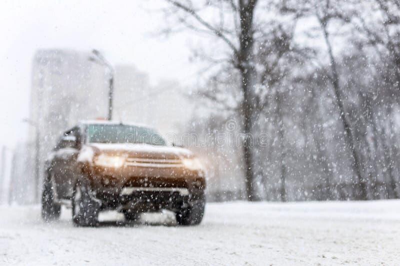 Ciężki opad śniegu i zamazany SUV awd samochód na drodze 4wd pojazd na miasto ulicie przy zimą Sezonowy pobocze pomocy pojęcie obraz stock