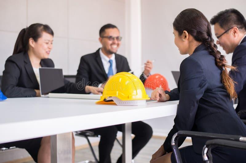 Ciężkich kapeluszy zbawczy hełm w pokoju konferencyjnym, Blured ludzie architekta i inżynier przy biurem fotografia royalty free