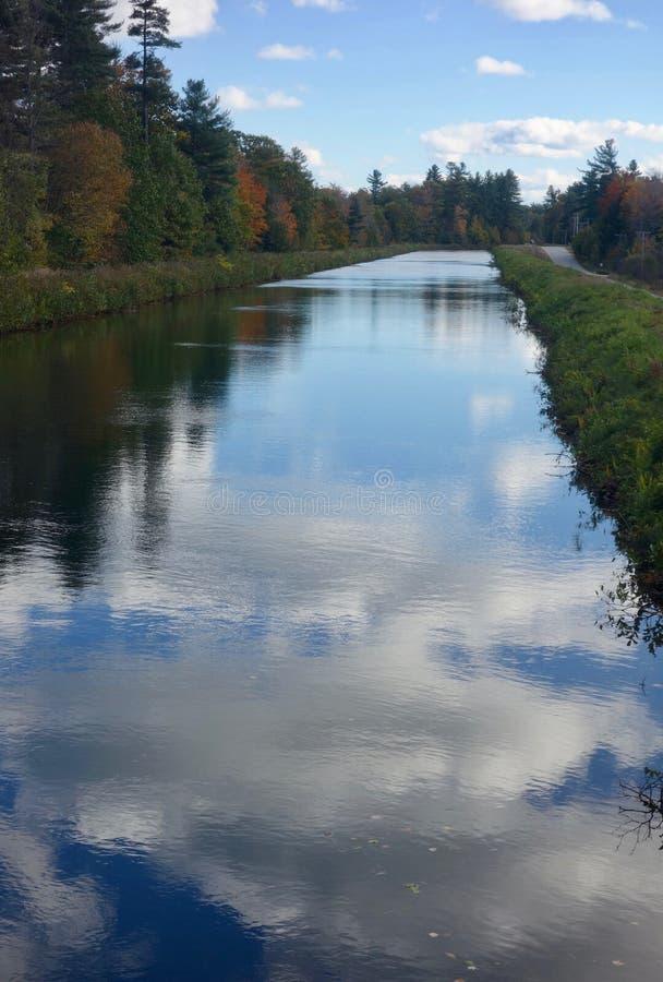 Ciężkie białe i popielate chmury nad głębokim błękitnym jeziorem na jesień dniu w Maine, usa zdjęcia stock
