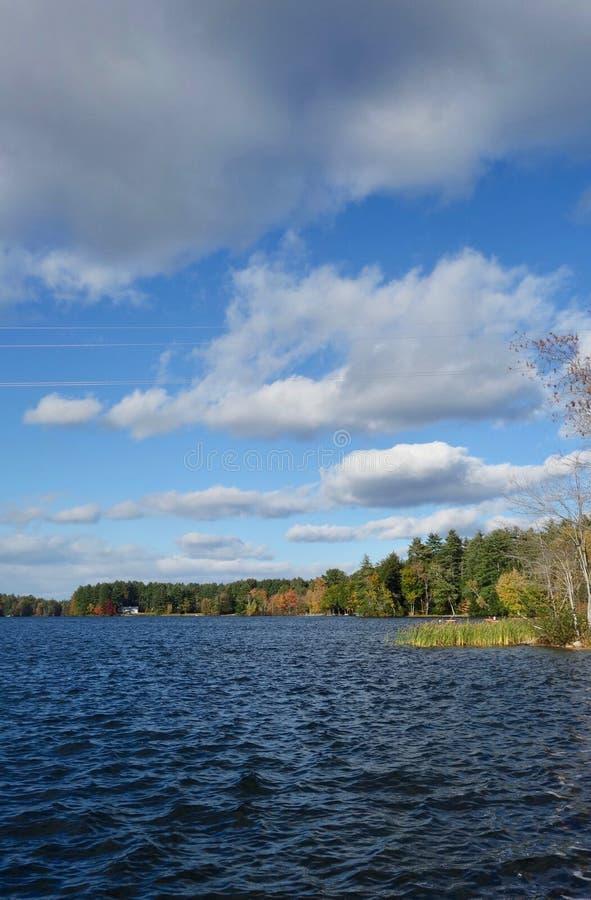 Ciężkie białe i popielate chmury nad głębokim błękitnym jeziorem na jesień dniu w Maine, usa fotografia royalty free