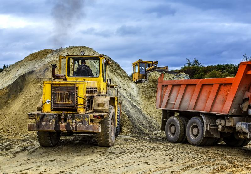 ciężkiego koło ekskawatoru maszynowy działanie przy zmierzchem, ładunki piasek w ciężarówkę obrazy stock