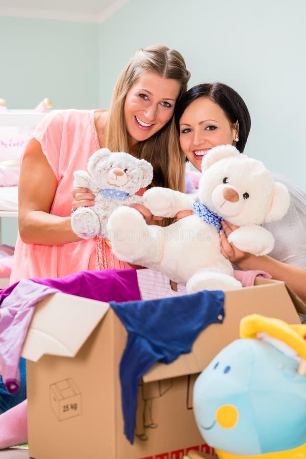 Ciężko kobieta w ciąży i przyjaciela ułożenia childs izbowi zdjęcia royalty free
