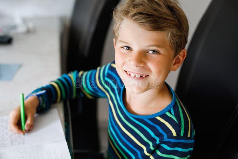 Ciężko pracujący szczęśliwy chłopak ze szkoły, który robi pracę domową w czasie kwarantanny z powodu choroby pandemii korony Zdro zdjęcia stock