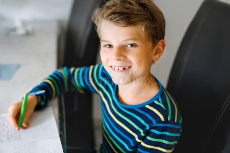 Ciężko pracujący szczęśliwy chłopak ze szkoły, który robi pracę domową w czasie kwarantanny z powodu choroby pandemii korony Zdro zdjęcie royalty free