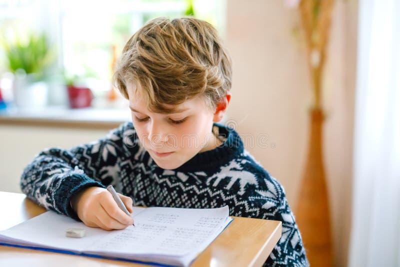 Ciężko pracujący szczęśliwy chłopak ze szkoły, który robi pracę domową w czasie kwarantanny z powodu choroby pandemii korony Zdro zdjęcie stock
