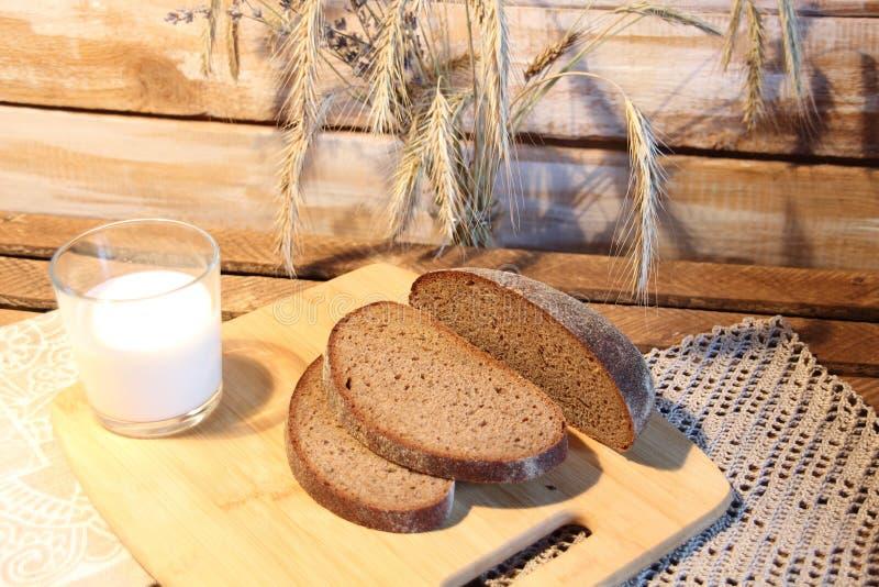 Cięcie brązowego chleba na desce drewnianej, szklanka mleka i przypraw w stylu rustycznym zdjęcia royalty free