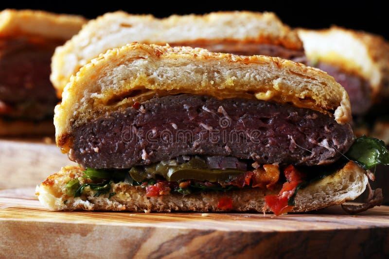 Cięcie w przyrodnim Angus hamburgerze na zbożowej babeczce z pomidorowym delicje, lettuc obrazy royalty free