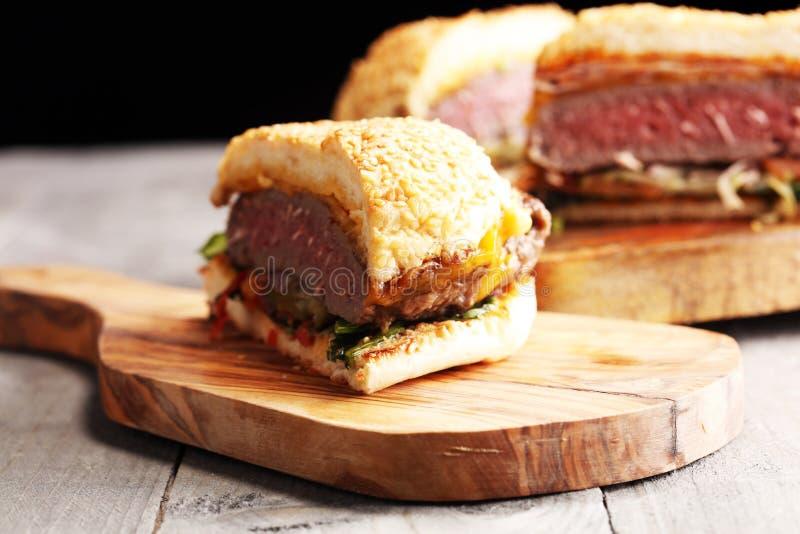 Cięcie w przyrodnim Angus hamburgerze na zbożowej babeczce z pomidorowym delicje, lettuc zdjęcia royalty free