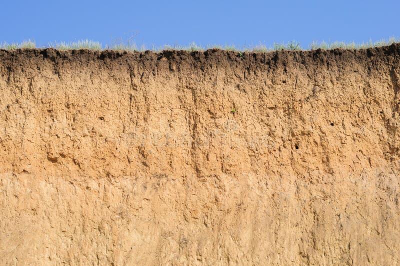Cięcie ziemia z różnymi warstwami, trawą i niebem, zdjęcie stock