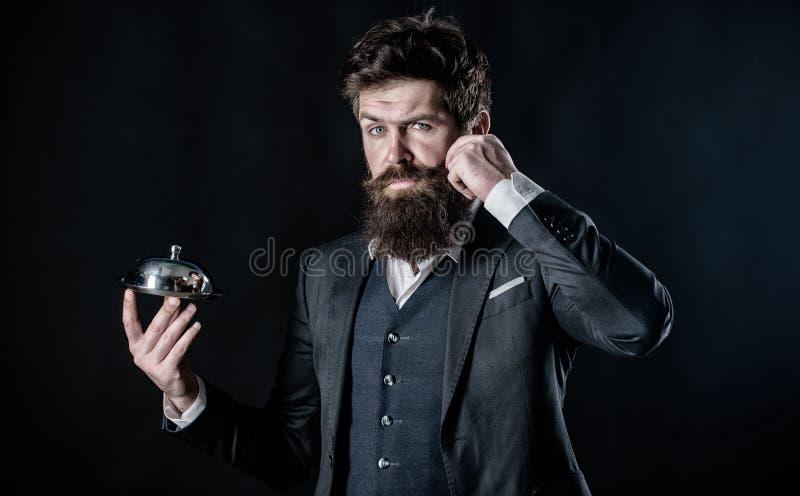 Ci? dovrebbe essere fine Cuoco unico barbuto dell'uomo che presenta pasto Uomo del cameriere Ricetta perfetta piatto metallico de immagine stock libera da diritti