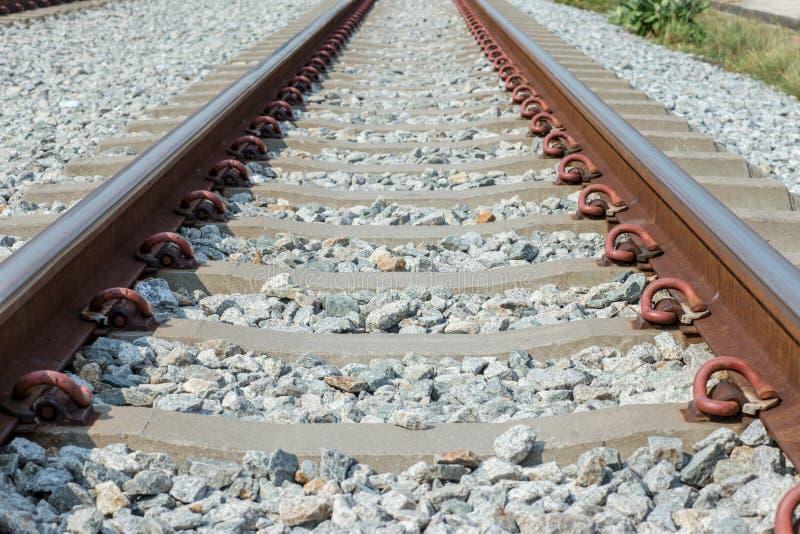 Ci?rrese encima de la junta del carril, ancla del carril con la l?nea de la perspectiva de pistas de ferrocarril Transporte de la fotografía de archivo