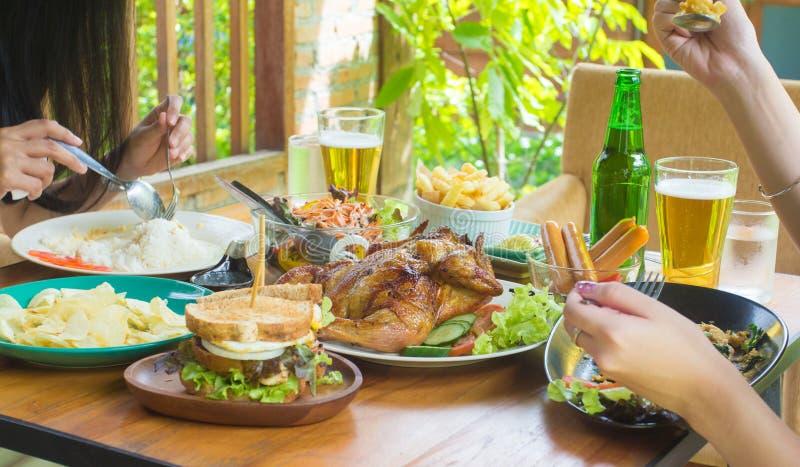 Ci?rrese encima de la mano, comiendo Grupo de personas que cena concepto, con la asación del pollo foto de archivo libre de regalías