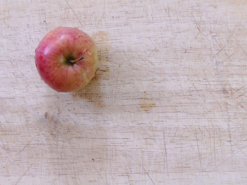 Ci?rrese encima de manzana roja en un tablero de madera desde arriba foto de archivo libre de regalías