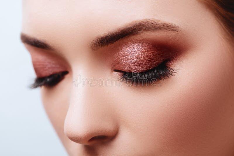 Ci?rrese encima de vista del ojo azul de la mujer con las sombras de oro hermosas y el maquillaje negro del l?piz de ojos fotos de archivo libres de regalías