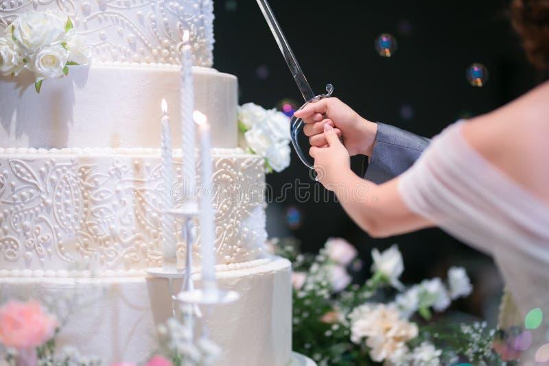 Ci?rrese hasta una parte del cuerpo de la novia y el novio est? cortando su pastel de bodas imagen de archivo